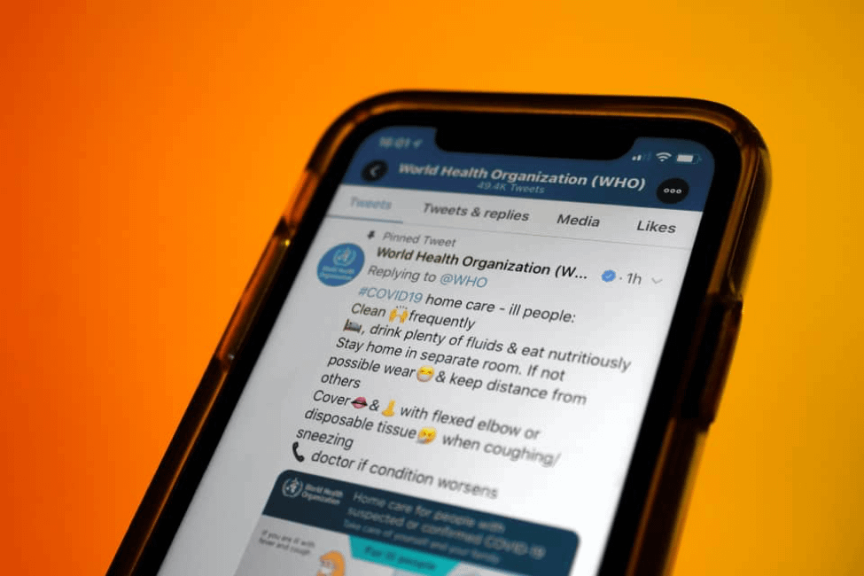 Phone showing tweets from World Health Organization